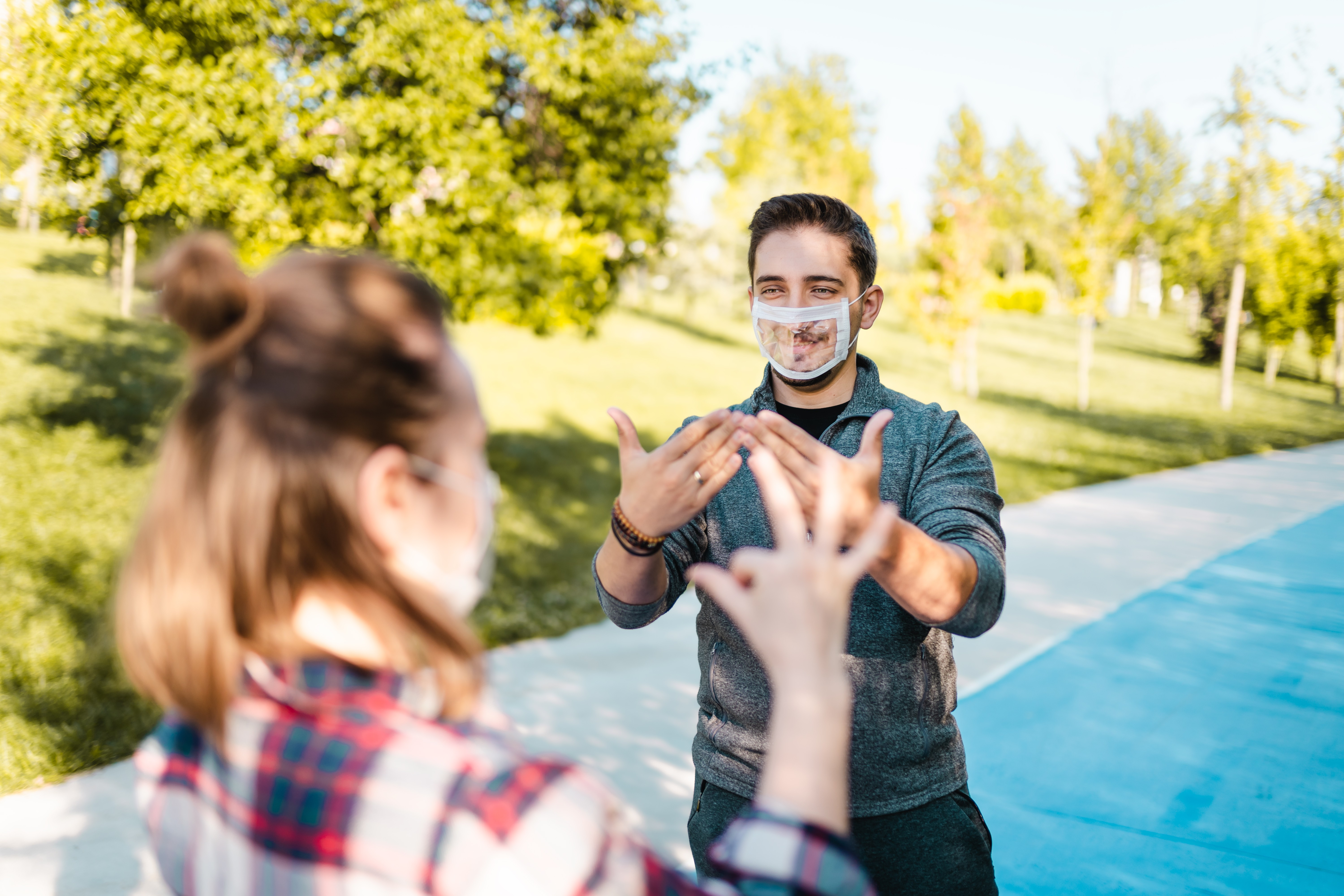 Two people standing outside communicating through sign language with a clear mask on the face