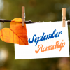 A note attached to a twig with clothes pins. A heart-shaped leaf is in the corner. the note reads September RoundUp