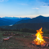 A campfire is in the foreground and mountains in the background with the dawn of the new day behind them